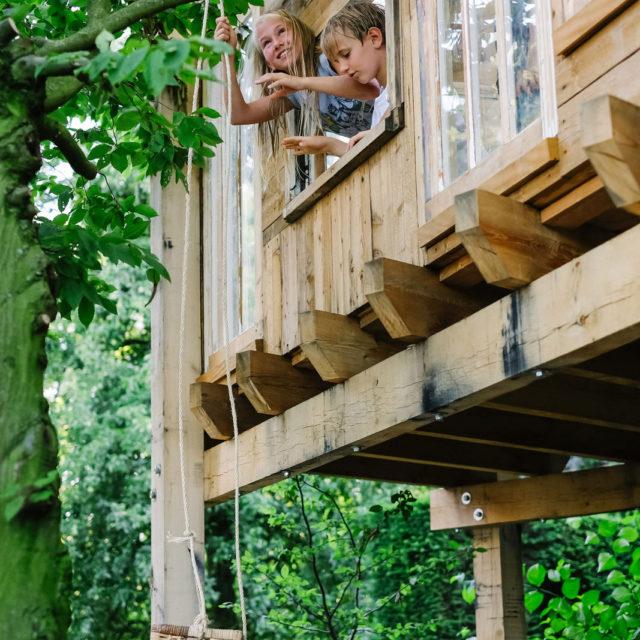 strakke boomhut met spelende kinderen