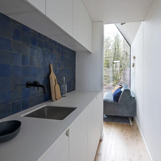 binnenschrijnwerk met witte keuken met blauwe fiances en zetel