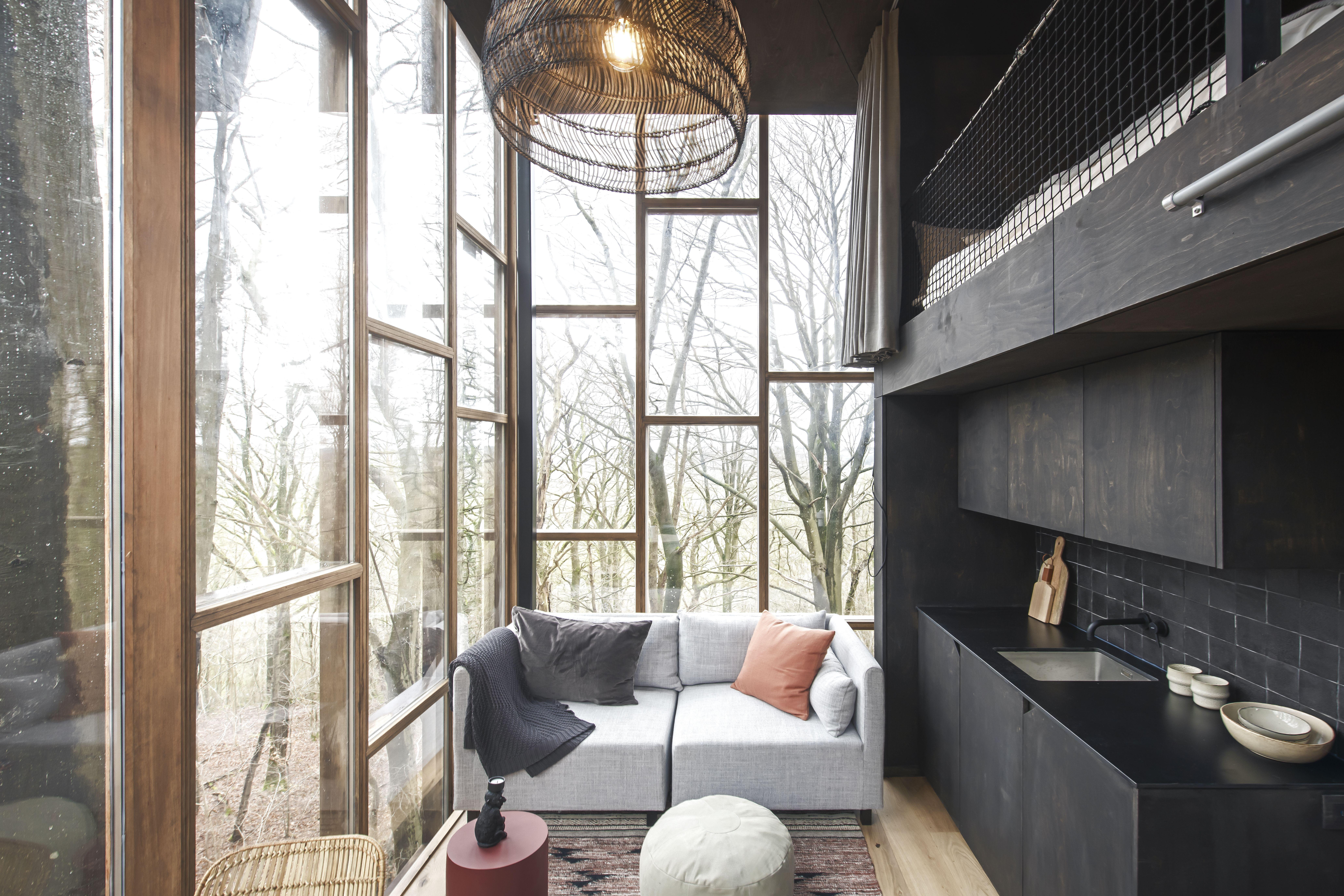 binnenschrijnwerk of interieur van een boomhut in een bos met veel glas en zwarte kasten