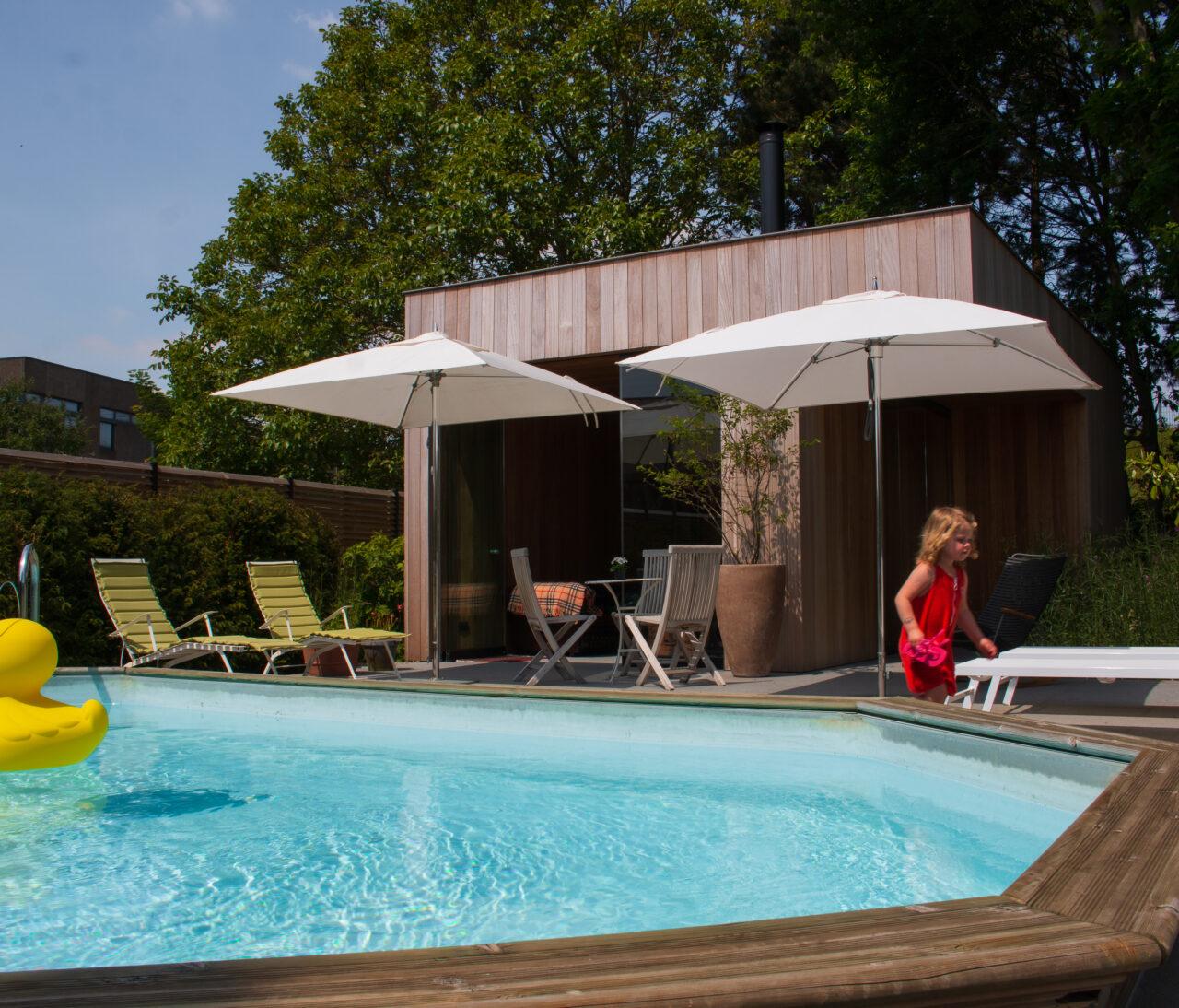 een poolhouse of tuinhuis bij een houten zwembad met kindje