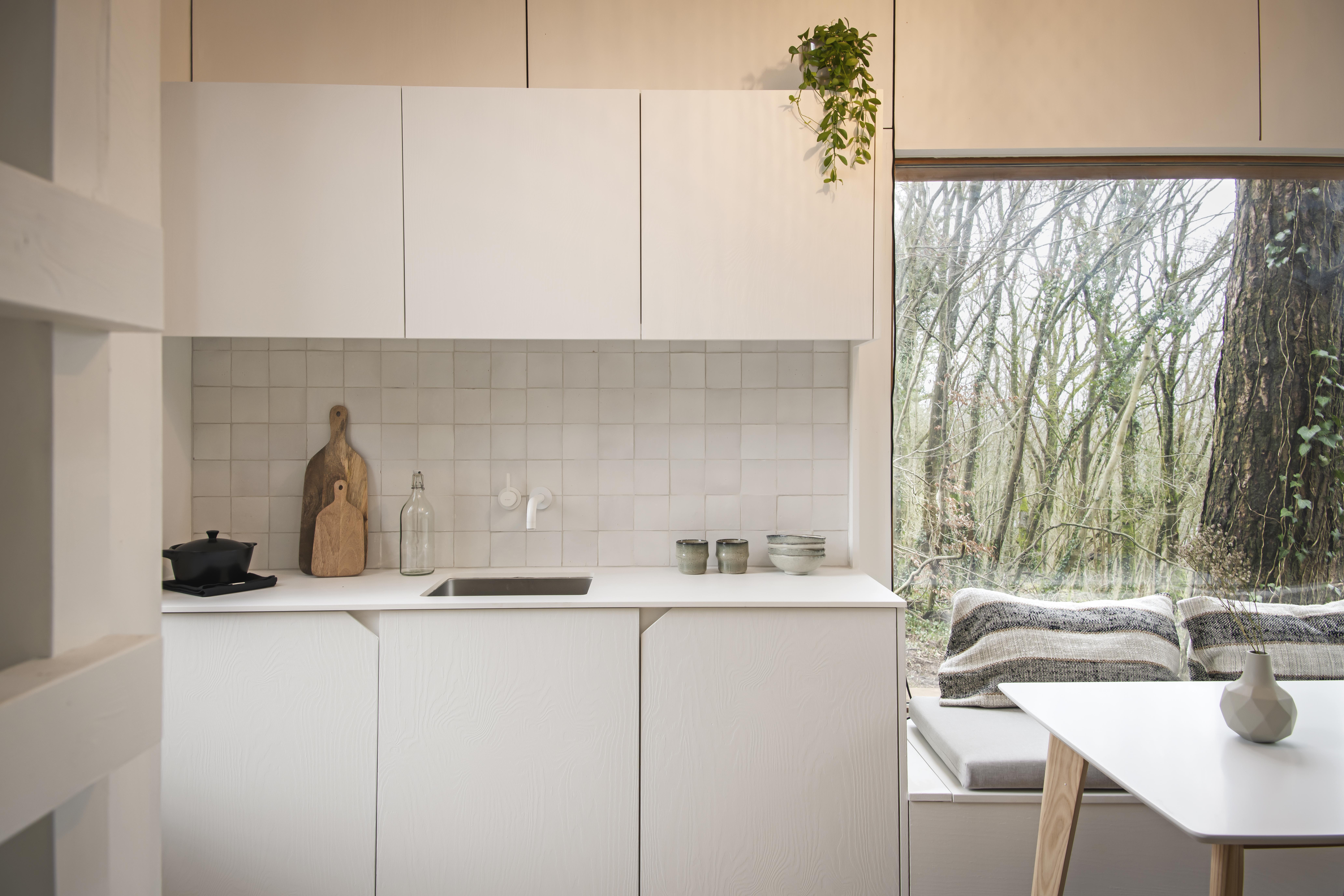houten woonunit met binnenschrijnwerk met witte keuken en witte keukentafel