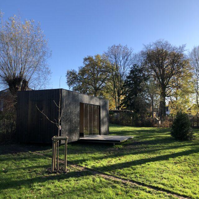 een zwart tuinkantoor in een tuin.
